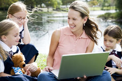 A teacher and children using a laptop outside Royalty Free Stock Images