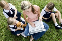 A teacher and children using a laptop outside Royalty Free Stock Photos
