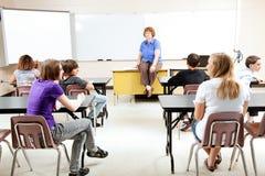 Teacher With Class. Teacher sitting on her desk, teaching a class of teenage students stock photo
