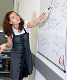 Teacher in classroom. At blackboard stock photography