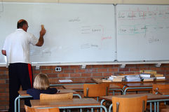 Teacher in classroom. An elderly caucasian white adult male teacher at work and a young little schoolkid in an almost empty classroom of a school. The student is stock photo
