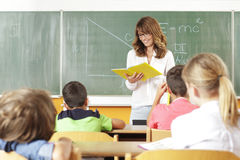 Teacher In Classroom. Elementary classroom setting. Focus on teacher and chalkboard Royalty Free Stock Images