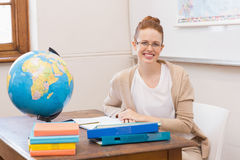 Teacher in classroom with globe Royalty Free Stock Photo