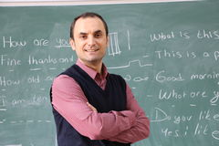 The teacher in the classroom on greenboard background. Male teachers show the board with his hand. teacher smiling. teacher in the classroom board cleaning Stock Image