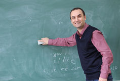 The teacher in the classroom on greenboard background. Male teachers show the board with his hand. teacher smiling. teacher in the classroom board cleaning Stock Photos