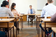 Teacher in classroom. Teacher sitting in classroom full of students during class royalty free stock photos
