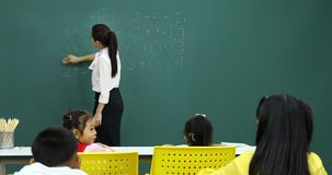 Teacher clean the board the have math problems. Asian female teacher clean the board the have math problems on it, in Math class stock video