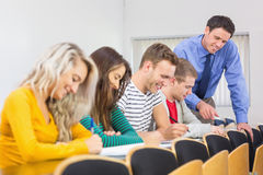 Teacher with college students at the classroom stock photography
