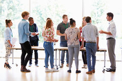 Teacher With College Students Standing By Desks In Classroom royalty free stock images