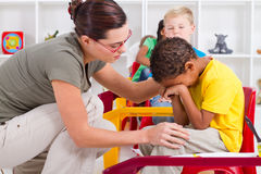 Teacher comfort student. A young preschool teacher giving comfort to a crying young boy student in classroom stock photo