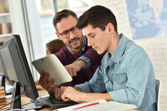 Teacher in computing class with student working on tablet. Teacher in computing class assisting teenager with tablet Royalty Free Stock Photos