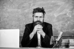 Teacher concentrated bearded mature schoolmaster listening with attention. Pay attention to details. Teacher formal wear. Sit table classroom chalkboard royalty free stock images