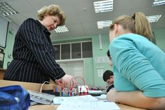 The teacher conducts laboratory work in physics in physics stock photos