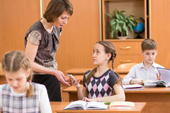 Teacher confiscating mobile phone at lesson in school Royalty Free Stock Photos