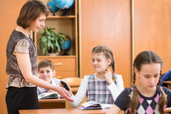 Teacher confiscating school kid's mobile phone at lesson Stock Image