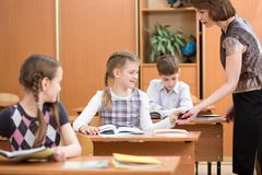 Teacher confiscating schoolkid`s mobile phone at lesson Royalty Free Stock Photos