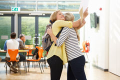 Teacher Congratulating Pupil On Successful Exam Result. By Hugging stock images