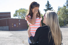 Teacher consoling a girl on  schoolyards Royalty Free Stock Photo