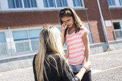 Teacher consoling a girl on  schoolyards Royalty Free Stock Photos