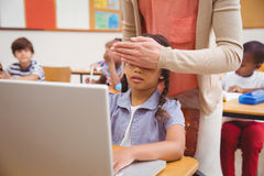 Teacher covering pupil eyes in front of the computer Royalty Free Stock Photos