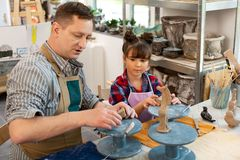 Teacher and cute girl sculpting little clay animals in art school stock image