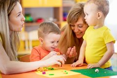 Teacher and cute little kids play with plasticine in preschool stock photos