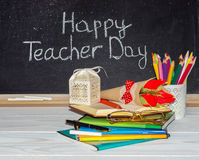Teacher  Day. Flowers and gift; copybooks on the teacher's desk. Royalty Free Stock Image