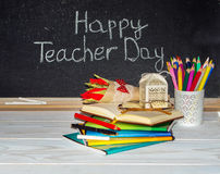Teacher  Day. Flowers and gift; copybooks on the teacher's desk. Stock Photo