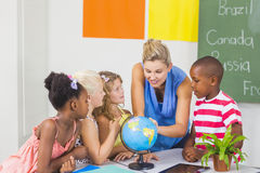 Teacher discussing globe with kids Royalty Free Stock Photo