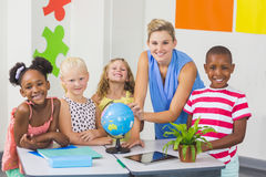 Teacher discussing globe with kids Stock Images