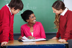 Teacher Discussing With Students At Desk. Young female teacher discussing with students at desk in classroom Stock Photo