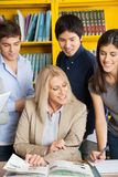 Teacher Discussing With Students At Table In Royalty Free Stock Photos