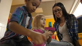 Teacher with diverse kids playing with didactic toys. Portrait of beautiful teacher with multinational diverse kids playing with colorful didactic toys in