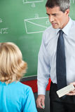 Teacher With Duster And Chalk Looking At Boy Stock Photo