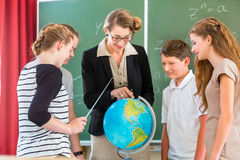 Teacher educate students  having geography lessons in school. Students or pupils having group work while geography lesson and the teacher test or educate them in Royalty Free Stock Photography