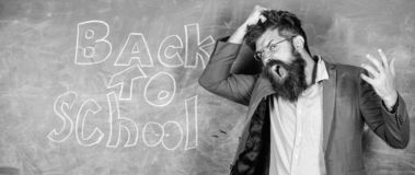 Teacher or educator stands near chalkboard with inscription back to school. Hate school. Teacher unhappy shouting. Hysterically face. Teacher goes mad about royalty free stock photography
