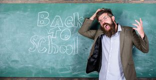 Teacher or educator stands near chalkboard with inscription back to school. Teacher unhappy shouting hysterically face. Man refuses begin work at school. Hate stock photo