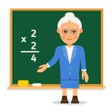Teacher. Elderly female teacher stand on lesson at the blackboar. D in classroom. Professor showing elementary example. Tutor points а hand at the calculations Royalty Free Stock Photography