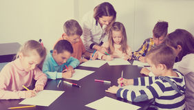 Teacher and elementary age children drawing at classroom. In school Royalty Free Stock Images