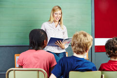 Teacher in elementary school class. Reading from a notebook Royalty Free Stock Image