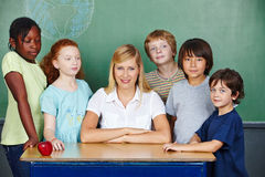 Teacher with elementary school. Teacher at desk with elementary school students in front of chalkboard Royalty Free Stock Photography
