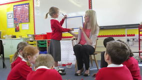 Teacher With Elementary School Pupils In Lesson. Female pupil stands at the front of class with teacher and write on whiteboard.Shot on Canon 5d Mk2 with a frame stock footage