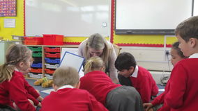 Teacher With Elementary School Pupils In Lesson. Pupils playing with plastic letters as teacher holds magnetic board.Shot on Canon 5d Mk2 with a frame rate of stock video