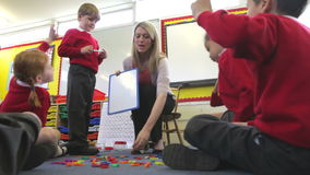 Teacher With Elementary School Pupils In Lesson. Pupils playing with plastic letters as teacher holds magnetic board.Shot on Canon 5d Mk2 with a frame rate of stock video footage