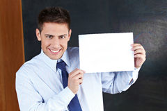 Teacher with empty white sign. Smiling teacher with empty white sign in front of chalkboard Stock Images