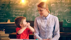 A teacher is engaged in drawing with a boy in a school classroom against a background of a green board. concept of stock video
