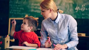 Teacher is engaged with a young boy in the school class. School children in uniform. Teacher in classroom. Teacher and stock footage