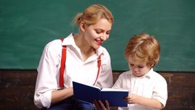 Teacher is engaged with a young boy in the school class. School children in uniform. Teacher in classroom. Teacher and stock video footage