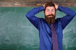 Teacher etiquette tips modern education professional. Man bearded teacher or educator hold head chalkboard background royalty free stock image