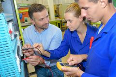 Teacher evaluating students working on electrical circuits. 2 Royalty Free Stock Photography